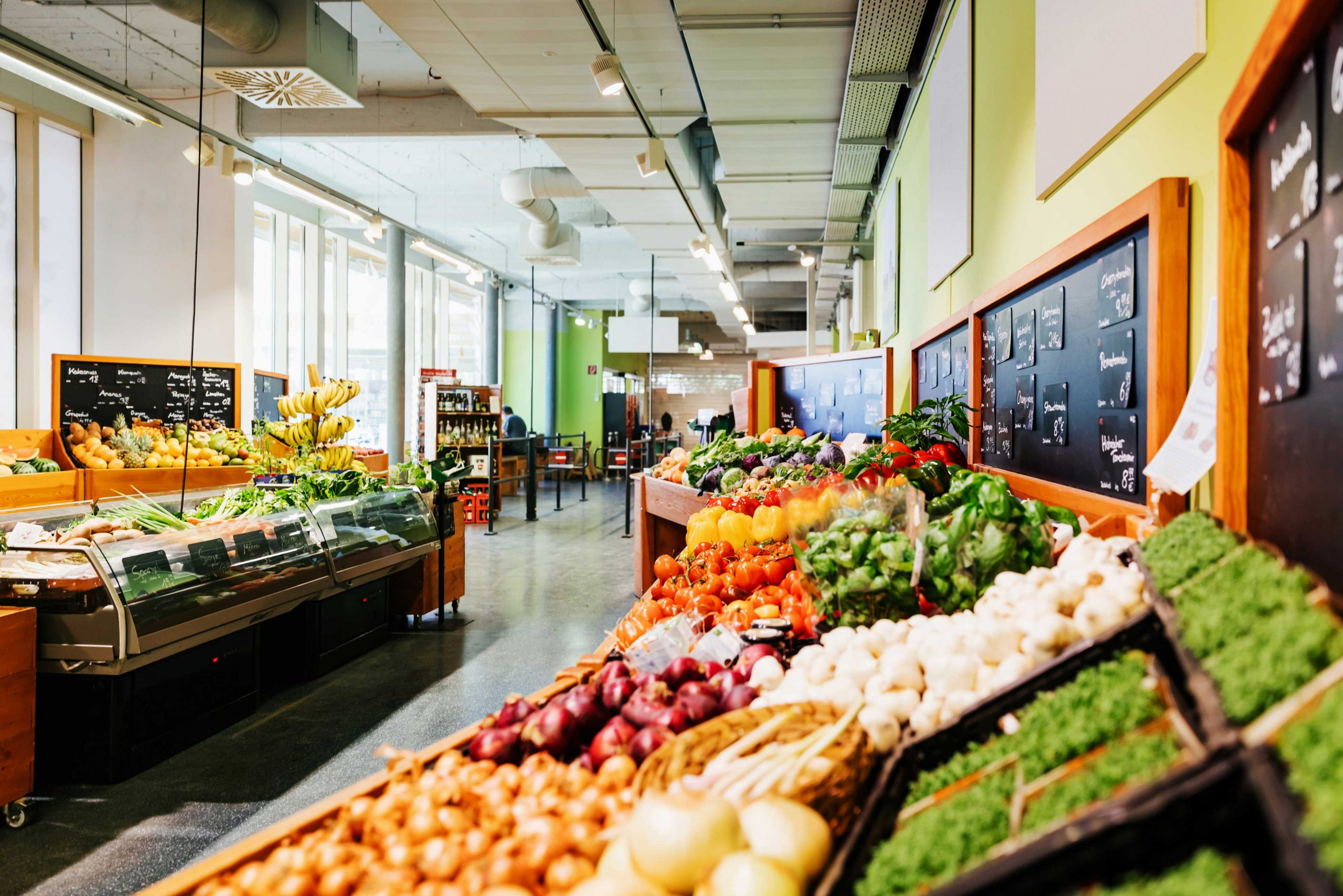 The vegetable aisle filled with various food items and fridges